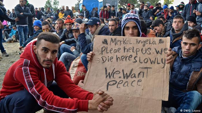 Asylum seekers-hold a sign asking Angela Merkel for help