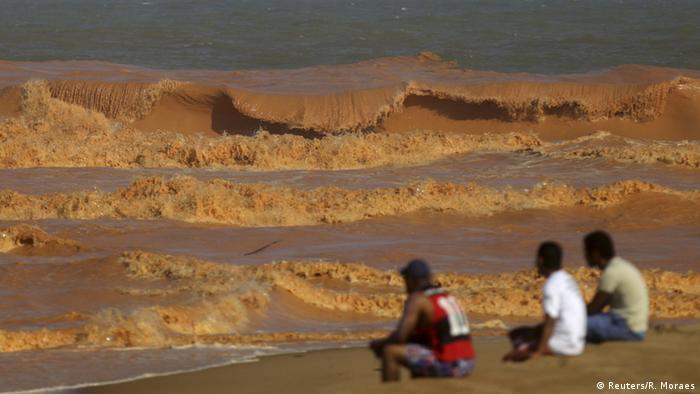 Personen sitzen am Strand von Povoacao und blicken braune Wellen an (Foto: Reuters/R. Moraes)