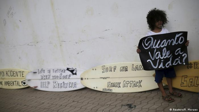 A boy holds protest sign reading How much is life worth? in Regencia village (Photo: Reuters/R. Moraes)