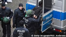 29.11.2015 Policeman march off a refugee at the former airport Tempelhof that now hosts refugees in Berlin, on November 29, 2015 after a brawl erupted among refugees. Clashes broke out between hundreds of asylum seekers armed with knives and sticks at a shelter in Berlin, in the second mass brawl to erupt over the weekend at crowded migrant accommodations in Germany. Copyright: Getty Images/AFP/O. Andersen