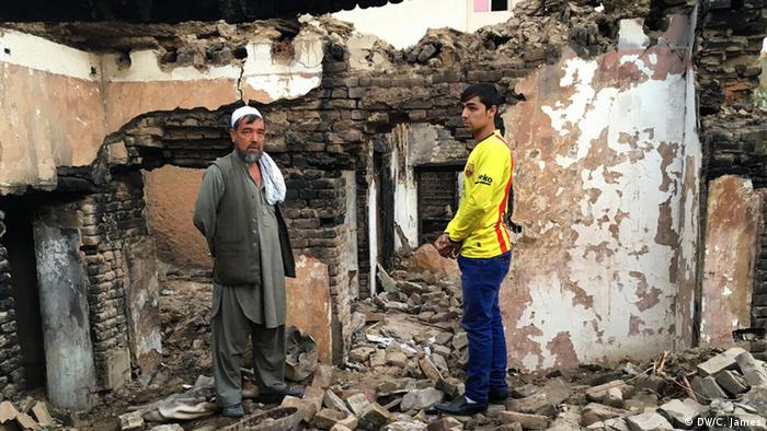 Zalmai Nabizoda stands with one of his eight children in what is left of their family home in Kunduz