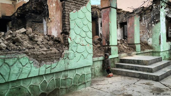 Zalmai Nabizoda's niece stands in front of his former home