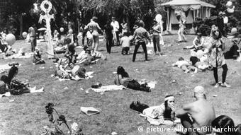 Hippies liegen 1967 auf einer Wiese im Park, um sie herum liegt Müll