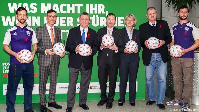 Gruppenbild mit Ball - Gesundheitsminister Gröhe (3. v. l.) mit Vertretern der Aids-Hilfen, Sportverbänden und zwei Rugbyspielern