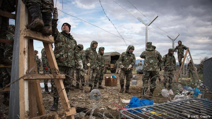 Men in camouflage gear erect part of Macedonian's border fence near Idomeni, Greece