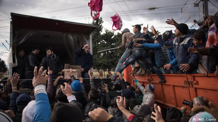 Members of a Greek workers' union distribute supplies to asylum-seekers