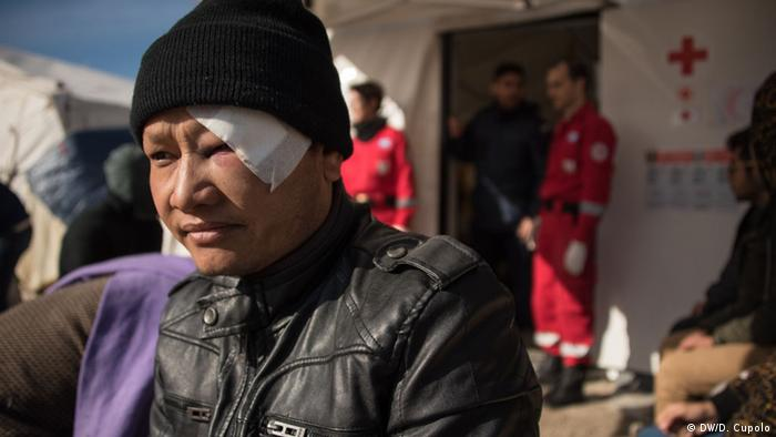 A Nepalese man with a bandaged swollen eye sits outside a first aid tent