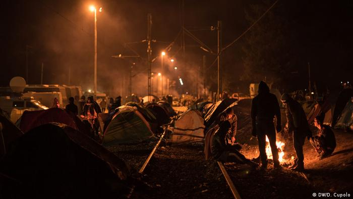 A nighttime scene of pitched tents along railroad tracks and people warming themselves at a campfire