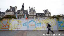A man walks past the exhibition Paris de L'Avenir, a showcase for tangible climate solutions in the context of the COP21 World Climate Summit, in front of Paris city hall, France, November 30, 2015, as the World Climate Change Conference 2015 (COP21) started today in Le Bourget. REUTERS/Eric Gaillard Reuters/E.Gaillard