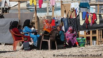 Women sit outside a tent in a refugee camp in Lebanon