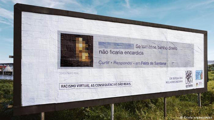 A billboard shows a Brazilian social media comment written in Portuguese