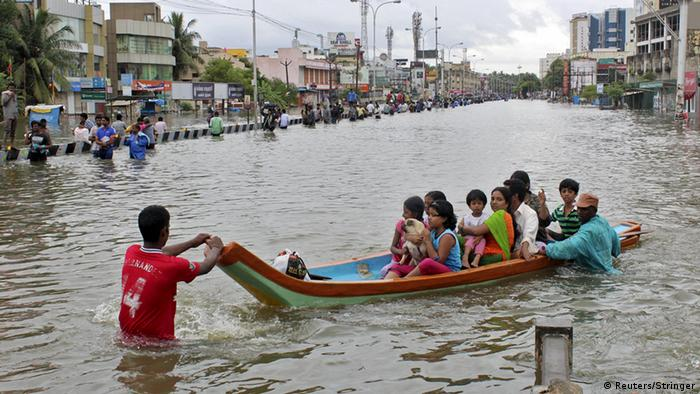 A man leads a canoe through flood waters in India