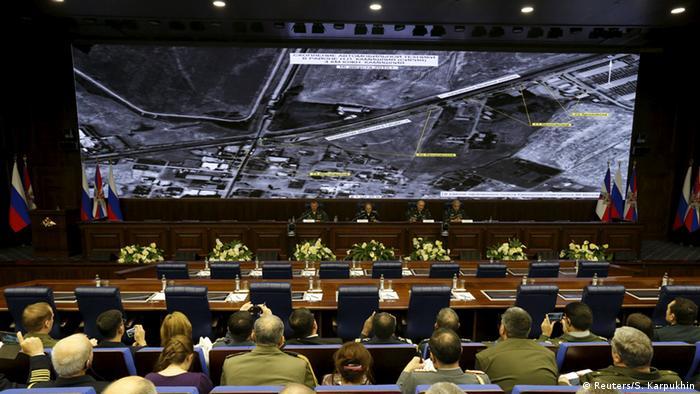 Offiziere des russischen Verteidigungsministeriums sitzen unter Bildschirm mit Satellitenaufnahmen (Foto: Reuters)