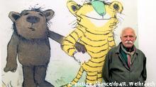 Janosch vor einem Bild mit dem kleinen Bären und dem kleinen Tiger