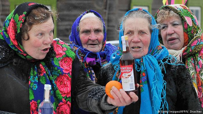 Old women with colorful head scarves hold out an orange and a bottle of alcohol