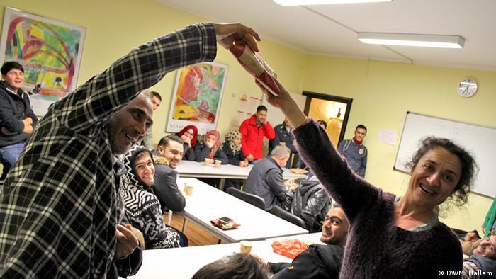 Deutschland Deutschkurs für Flüchtlinge in Bonn Lehrerin Alev Erisöz Reinke mit Radwan Ajouz