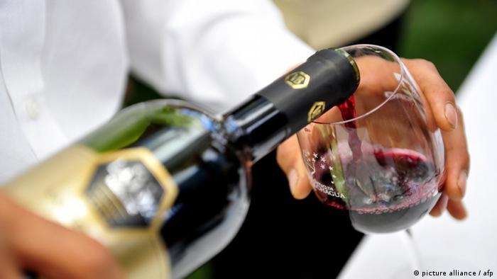 Gießen des Rotweines in einem Glas