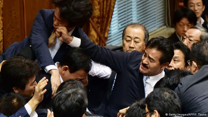 Japanese lawmakers fight at the Upper House's ad hoc committee session.