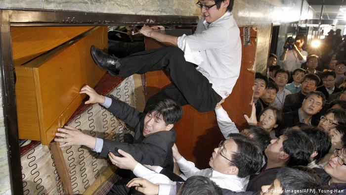 South Korean opposition party member try to enter a parliamentary committee room barricaded by ruling party legislators.