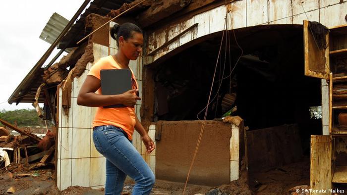 À espera de nova moradia, Alecsandra Martins da Silva confere o pouco que restou de sua casa em Bento Rodrigues