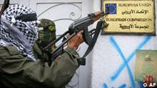 Palestinian masked militants of the Al-Yasser Brigades, a militia linked to the Fatah movement, left, and of the Islamic Jihad, second left, point their guns to the European Union emblem outside the EU Commission's office in Gaza City Thursday Feb. 2, 2006. A group of gunmen briefly took up position outside the office Thursday in protest over a newspaper cartoon that has riled the Muslim world. (AP Photo/Adel Hana)