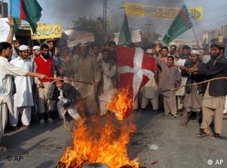 Pakistani religious students burn the Danish flag on Thursday