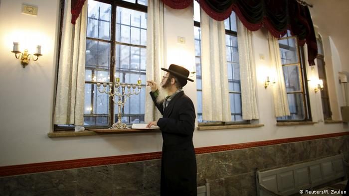 An Ultra-Orthodox Jewish man lights candles on the first night of the holiday of Hanukkah