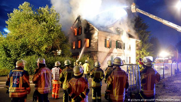 Firefighters try to extinguish the flames in a burning house that was planned to be converted into a shelter for asylum seekers in Weissach, southern Germany
