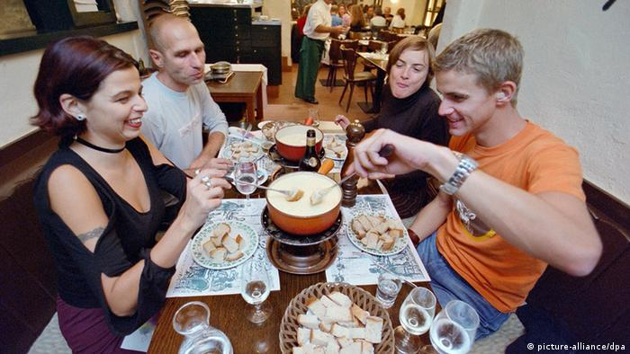 Two couples sitting around cheese fondue