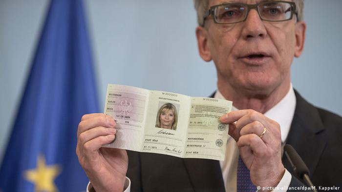 глава МВД Германии Томас де Мезьер демонстрирует новое удостоверение беженца
