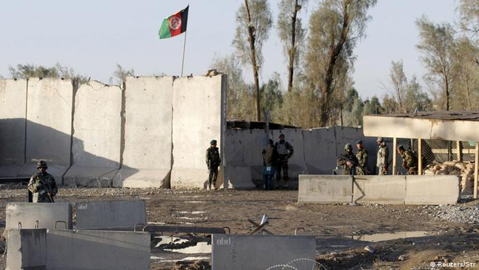 Afghan security forces stand guard at the entrance to Kandahar airport after an attack in 2015