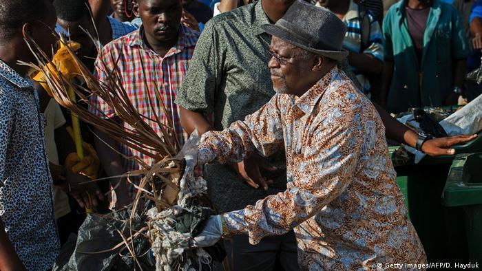 Tansania President John Magufuli cleaning up a street.