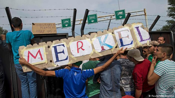 Migrants at the Hungarian border hold up a banner reading M-E-R-K-E-L
