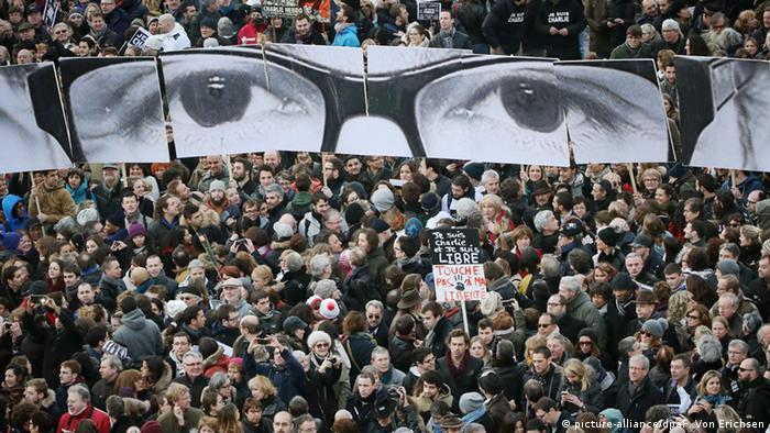 Der kritische Blick von Charb wacht als Plakat über der Demonstration für Meinungs- und Pressefreiheit in Paris am 11. Januar 2015 (Bild: picture-alliance/dpaF. Von Erichsen)
