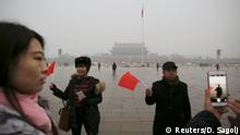 09.12.2015 *** People with national flags have their picture taken just after a flag-raising ceremony amid heavy smog at Tiananmen Square, after the city issued its first ever red alert for air pollution, in Beijing December 9, 2015. REUTERS/Damir Sagolj Reuters/D. Sagolj