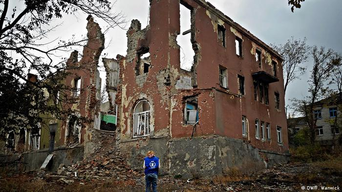 A local WFP worker stands in front of a shelled house on the outskirts of Slovyansk