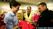 11. Dez 2015 Syrian refugees are presented with a child's winter jacket by Canada's Prime Minister Justin Trudeau (L) on their arrival from Beirut at the Toronto Pearson International Airport in Mississauga, Ontario, Canada December 11, 2015. After months of promises and weeks of preparation, the first Canadian government planeload of Syrian refugees landed in Toronto on Thursday, aboard a military aircraft met by Prime Minister Justin Trudeau. REUTERS/Mark Blinch