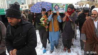 تصویر مهاجران افغان در مراسم تشییع جنازه. دو نفر از آنها یکی در هوای برفی صندل تابستانی به پا دارد و دیگری پلاستک به پا کشیده و دمپایی پا کرده است.
