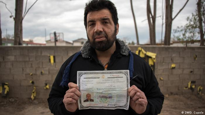 Payman Qasimian, an Iranian asylum seeker, holds up his father's US naturalization document. He says he lived in the states for 15 years before getting arrested in Iran and being stripped of his papers (Photo: DW/ Diego Cupolo)