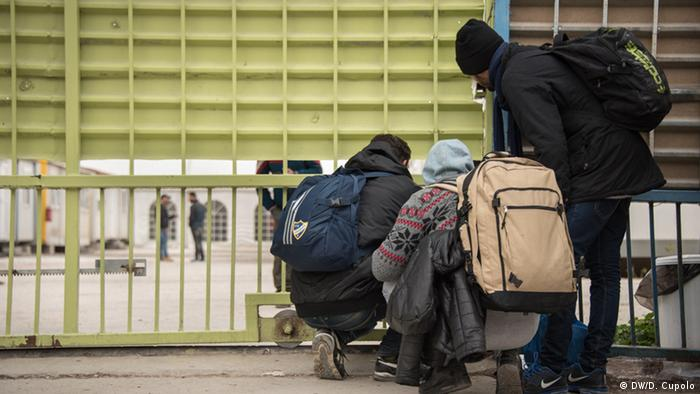 Moroccan asylum-seekers peer under the gates at Eleonas Refugee Camp, which was at maximum capacity on Friday afternoon, after receiving new arrivals from the Greek border (Photo: DW/Diego Cupolo)
