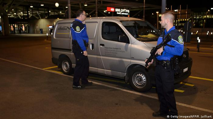 Security officers check a van at Geneva's airport after police raised the alert level