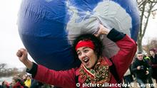 11.12.2015 *** epa05066314 A woman carries an inflatable earth as thousands of people demonstrate in front of the Eiffel Tower for climate change in Paris, France, 12 December 2015. The 21st Conference of the Parties (COP21) is held in Paris from 30 November to 11 December aimed at reaching an international agreement to limit greenhouse gas emissions and curtail climate change. EPA/ETIENNE LAURENT +++(c) dpa - Bildfunk+++ picture-alliance/dpa/E. Laurent