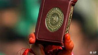 A woman holds a copy of the Koran