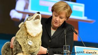 German Chancellor Angela Merkel holds a stuffed wolf (Getty Images/AFP/T. Kienzle)