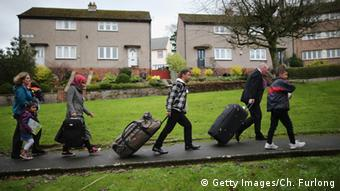 four people pulling luggage along a street Copyright: Getty Images/Ch. Furlong