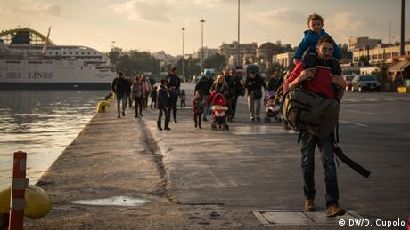 Adults and children walk along the pier in Piraeus, Greece
