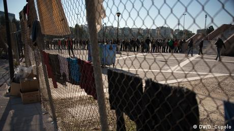 Male asylum-seekers lined up in the taekwondo stadium, Athens