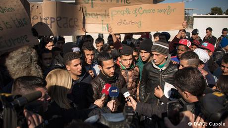 Journalists hold microphones in front of a young man surrounded by other asylum-seekers