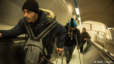 Two men on crutches ride up an escalator in a metro station in Athens