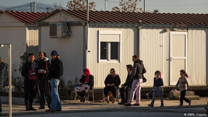 Adults and children stand and sit outside two trailers in Eleonas camp in Athens